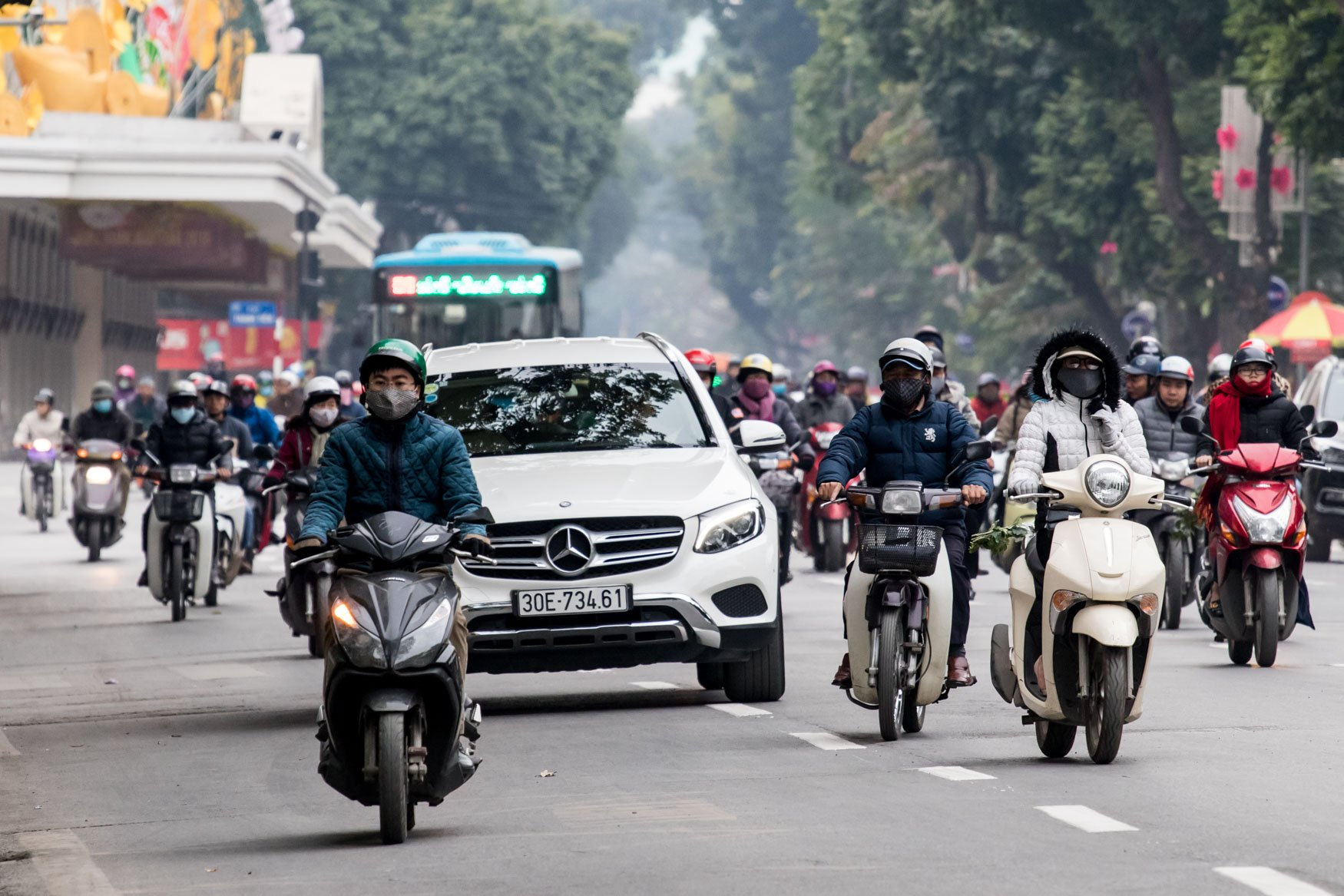 Scooters and a Mercedes in Hanoi